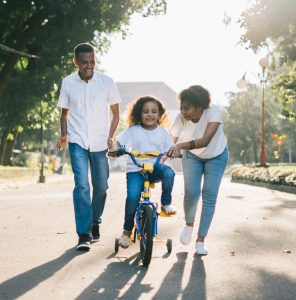 Healthy family teaching daughter to ride bike
