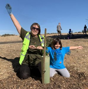 Mother and daughter planting an oak seedling